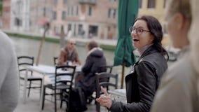 Υπαίθριος πυροβολισμός των όμορφων μοντέρνων κοριτσιών που παίρνουν έναν συμπαθητικό περίπατο στη Βενετία το καλοκαίρι απόθεμα βίντεο