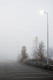 Υπαίθριος σταθμός αυτοκινήτων που καλύπτεται στην πάχνη και την ομίχλη ξημερωμάτων Στοκ Φωτογραφίες