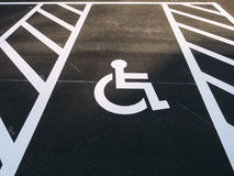 Υπαίθριος χώρος στάθμευσης υπαίθριων σταθμών αυτοκινήτων προτεραιότητας σημαδιών αναπηρικών καρεκλών ανικανότητας Στοκ Φωτογραφίες