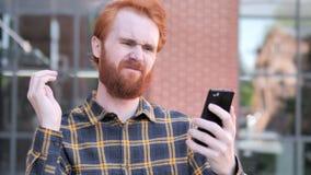 Υπαίθριος Redhead νεαρός άνδρας γενειάδων που ανατρέπεται από την απώλεια χρησιμοποιώντας Smartphone φιλμ μικρού μήκους