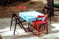 Υπαίθριο θερινό πεζούλι εστιατορίων - εκλεκτής ποιότητας καφές με τον παλαιό μπλε πίνακα με τις μαύρες και κόκκινες καρέκλες Στοκ φωτογραφία με δικαίωμα ελεύθερης χρήσης