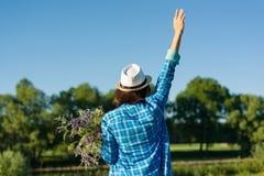 Υπαίθριο θερινό πορτρέτο της γυναίκας με την ανθοδέσμη των wildflowers, καπέλο αχύρου Η άποψη από τον πίσω, θηλυκό αύξησε το χέρι Στοκ Εικόνες