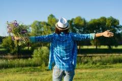 Υπαίθριο θερινό πορτρέτο της γυναίκας με την ανθοδέσμη των wildflowers, καπέλο αχύρου Η άποψη από τον πίσω, θηλυκό αύξησε το χέρι Στοκ Εικόνα