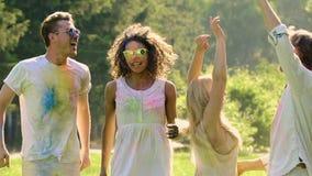 Υπαίθριο κόμμα, χαρούμενοι νέοι φίλοι που πηδά και που χορεύει στο φεστιβάλ Holi απόθεμα βίντεο