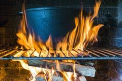 Υπαίθριο μαγείρεμα σε ένα κύπελλο του ανοξείδωτου πέρα από μια καίγοντας πυρκαγιά κοντά επάνω Έννοια του καλοκαιριού που ψήνει στ Στοκ Φωτογραφία