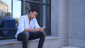 Υπαίθριο ξεφύλλισμα σε Smartphone, καθμένος νέο μαύρο όμορφο άτομο Στοκ εικόνες με δικαίωμα ελεύθερης χρήσης