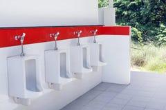 Υπαίθριο παλαιό άσπρο και κόκκινο χρώμα τουαλετών ουροδοχείων, η τουαλέτα του ατόμου με την άποψη τουαλετών από τα ουροδοχεία υπα στοκ φωτογραφία