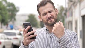 Υπαίθριο περιστασιακό άτομο γενειάδων που ανατρέπεται από την απώλεια χρησιμοποιώντας Smartphone απόθεμα βίντεο
