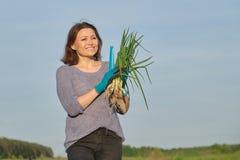 Υπαίθριο πορτρέτο άνοιξη της ώριμης γυναίκας με τα φρέσκα πράσινα κρεμμύδια στοκ εικόνα με δικαίωμα ελεύθερης χρήσης