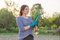 Υπαίθριο πορτρέτο άνοιξη της ώριμης γυναίκας με τα φρέσκα πράσινα κρεμμύδια στοκ εικόνες