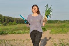 Υπαίθριο πορτρέτο άνοιξη της ώριμης γυναίκας με τα φρέσκα πράσινα κρεμμύδια στοκ φωτογραφία