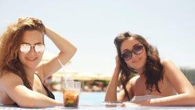 Υπαίθριο πορτρέτο δύο νέων χαριτωμένων φίλων στα γυαλιά ηλίου και των μαγιό με την κατάψυξη γυαλιού κοκτέιλ στην πισίνα φιλμ μικρού μήκους