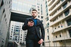 Υπαίθριο πορτρέτο ενός νέου επιχειρηματία με μια γενειάδα που χρησιμοποιεί ένα κινητό τηλέφωνο στο υπόβαθρο της σύγχρονης αρχιτεκ Στοκ Εικόνα