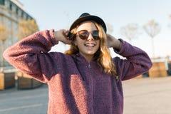 Υπαίθριο πορτρέτο ενός χαμογελώντας κοριτσιού εφήβων 13, 14 χρονών σε ένα καπέλο και γυαλιά ηλίου Υπόβαθρο πόλεων, χρυσή ώρα στοκ εικόνα