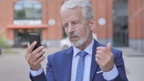 Υπαίθριο πορτρέτο επιχειρηματία που ανατρέπεται του παλαιού από την απώλεια σε Smartphone απόθεμα βίντεο