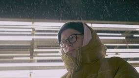 Υπαίθριο πορτρέτο κινηματογραφήσεων σε πρώτο πλάνο του νέου όμορφου ήρεμου μοντέρνου κοριτσιού που φορούν το δροσερό χειμερινό κα φιλμ μικρού μήκους