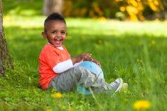 Υπαίθριο πορτρέτο μιας χαριτωμένης νεολαίας λίγο μαύρο αγόρι που παίζει με Στοκ Εικόνες
