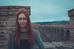 Υπαίθριο πορτρέτο της ελκυστικής νέας γυναίκας με την κόκκινη τρίχα που στέκεται στο κάστρο, μεσαιωνικό υδραγωγείο στο υπόβαθρο - Στοκ φωτογραφία με δικαίωμα ελεύθερης χρήσης