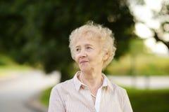 Υπαίθριο πορτρέτο της όμορφης ανώτερης γυναίκας με τη σγουρή άσπρη τρίχα Στοκ Φωτογραφία
