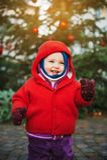 Υπαίθριο πορτρέτο του γλυκού λίγο 1χρονο κοριτσάκι που παίζει με το χριστουγεννιάτικο δέντρο Στοκ Φωτογραφίες
