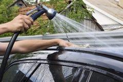 Υπαίθριο πλύσιμο αυτοκινήτων που χρησιμοποιεί τις μάνικες νερού Στοκ Εικόνα