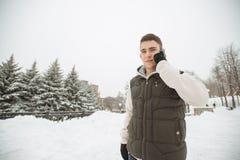 Υπαίθριο χειμερινό πορτρέτο για το νέο όμορφο άτομο με το τηλέφωνο Όμορφος έφηβος στην τοποθέτησή του σακακιών και φανέλλων σε μι Στοκ φωτογραφίες με δικαίωμα ελεύθερης χρήσης