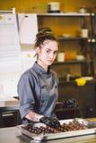 Υπαγόμενο επάγγελμα και μαγειρεύοντας ζύμη νέα καυκάσια γυναίκα με τη δερματοστιξία του αρχιμάγειρα ζύμης στην κουζίνα του εστιατ στοκ φωτογραφία με δικαίωμα ελεύθερης χρήσης