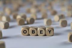 Υπακούστε - κύβος με τις επιστολές, σημάδι με τους ξύλινους κύβους στοκ φωτογραφία