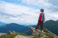 Υπερήφανες στάσεις αγοριών στον απότομο βράχο στα βουνά Στοκ Φωτογραφίες