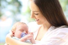 Υπερήφανη μητέρα με τον ύπνο μωρών της στοκ φωτογραφία