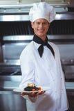 Υπερήφανος αρχιμάγειρας που κρατά ένα πιάτο των μακαρονιών μελανιού καλαμαριών Στοκ Φωτογραφίες