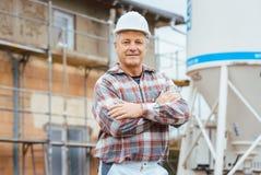 Υπερήφανος γυψαδόρος που στέκεται μπροστά από το ικρίωμα στο εργοτάξιο οικοδομής στοκ εικόνες με δικαίωμα ελεύθερης χρήσης