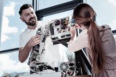 Υπερήφανος δάσκαλος που εξετάζει τη γυναίκα σπουδαστή που εργάζεται στο ρομπότ Στοκ Φωτογραφίες