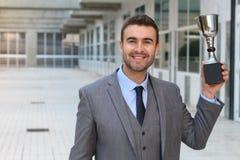 Υπερήφανος επιχειρηματίας που κρατά το τρόπαιό του στοκ εικόνα