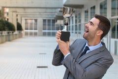 Υπερήφανος επιχειρηματίας που κρατά το τρόπαιό του στοκ εικόνες