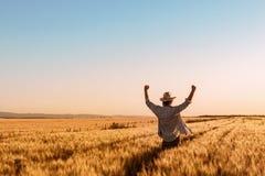 Υπερήφανος ευτυχής νικηφορόρος αγρότης σίτου με τα χέρια που αυξάνονται στο Β στοκ εικόνα