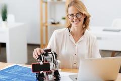 Υπερήφανος μηχανικός που αντιπροσωπεύει τη φουτουριστική εφεύρεσή της στο εσωτερικό στοκ εικόνες
