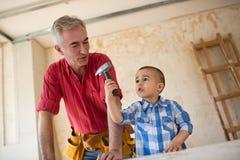 Υπερήφανος παππούς που προσέχει τον εγγονό του στο εργαστήριο Στοκ Εικόνα