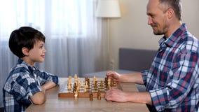 Υπερήφανος πατέρας που εξετάζει το χαριτωμένο γιο του που κερδίζει τον στο παιχνίδι σκακιού, αγαπημένο χόμπι στοκ εικόνα με δικαίωμα ελεύθερης χρήσης
