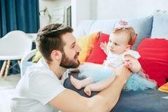 Υπερήφανος πατέρας που κρατά την κόρη μωρών του στο σπίτι στοκ εικόνες