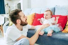 Υπερήφανος πατέρας που κρατά την κόρη μωρών του στο σπίτι στοκ εικόνα με δικαίωμα ελεύθερης χρήσης