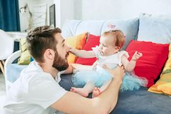 Υπερήφανος πατέρας που κρατά την κόρη μωρών του στο σπίτι στοκ εικόνες με δικαίωμα ελεύθερης χρήσης