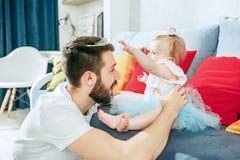 Υπερήφανος πατέρας που κρατά την κόρη μωρών του στο σπίτι στοκ φωτογραφία με δικαίωμα ελεύθερης χρήσης
