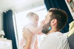 Υπερήφανος πατέρας που κρατά τη νεογέννητη κόρη μωρών του επάνω στον αέρα στο σπίτι στοκ εικόνες