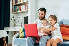 Υπερήφανος πατέρας που κρατά τις κόρες μωρών του στο σπίτι στοκ φωτογραφίες