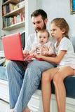 Υπερήφανος πατέρας που κρατά τις κόρες μωρών του στο σπίτι στοκ εικόνα με δικαίωμα ελεύθερης χρήσης