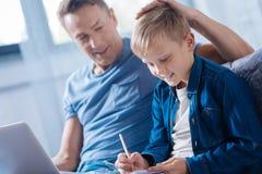 Υπερήφανος πατέρας που κτυπά ελαφρά το γιο στο κεφάλι ενώ αυτός που μελετά στοκ εικόνα
