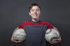 Υπερήφανος, χαμογελώντας έφηβος που κρατά της σφαίρας ποδοσφαίρου δύο στοκ εικόνες