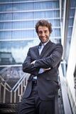 Υπερήφανο επιχειρησιακό άτομο που στέκεται μπροστά από το γραφείο του Στοκ Εικόνες