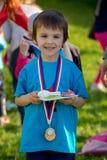 Υπερήφανο προσχολικό αγόρι, που κρατά τα βραβεία και τα μετάλλια στοκ εικόνες